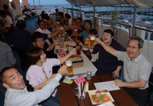 ビールジョッキを手に乾杯する来店客=25日、奄美市のホテルビッグマリン奄美