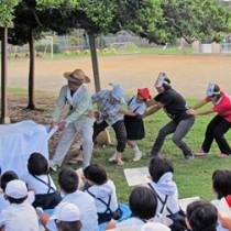 校内にある「日本一のガジュマル」の下であった昨年の緑陰読書会=2015年8月、和泊町の国頭小学校