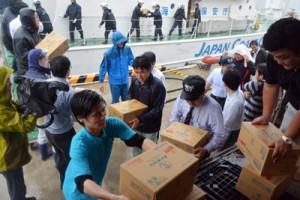 物資を巡視船に積み込む奄美市、奄美海保の職員ら=18日、名瀬港3号岸壁