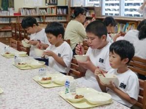 給食を食べる田検小の子どもたち(同校提供)=資料写真