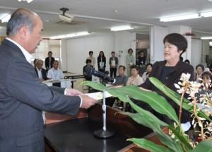 福山副市長から委嘱状を受け取る推進員(右)=12日、奄美市役所