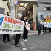 横断幕を掲げて事件に抗議する参加者=27日、奄美市