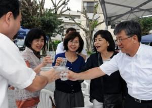 黒糖焼酎で乾杯する来場者=10日、奄美市名瀬のかねく公園