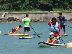 アマニコカヌークラブが4月から開き、好評を得ているカヌー、SUPの無料体験教室=4月、奄美市名瀬の朝仁海岸(提供写真)