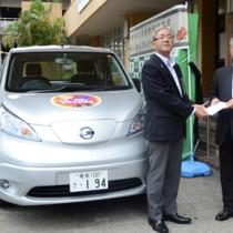 目録を受け取る朝山市長(右)と、貸与された電気自動車=30日、奄美市役所
