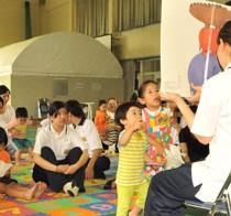 こども・かいご福祉学科の学生による絵本の読み聞かせを楽しむ子どもたち=24日、奄美看護福祉専門学校