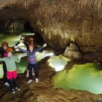 洞窟を探検する知名中学校の生徒たち=16日、知名町上平川(沖永良部島ケイビングガイド連盟提供)