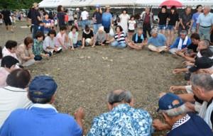 八月踊り唄に合わせて行った石打ち遊び(上)。老若男女が参加して先人たちの暮らしに思いをはせた=26日、龍郷町戸口