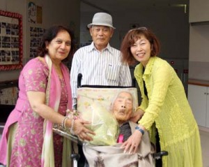 田島ナビさん(手前中央)を、孫の上中野真由美さん(右)や5男の俊彦さん(奥)とともに訪問し、長寿の秘訣や日本女性の生き方に迫ったアダルシュ・シャルマさん(左)=喜界町