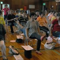 椅子に座って「キック」運動をする参加者=24日、瀬戸内町