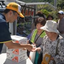 販売開始から20分で完売した果実の販売コーナー(左)と人気を集めた「すももスムージー」作り=19日、大和村大棚