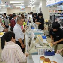 レジに並んだ買い物客の対応に追われる店員ら=15日午前7時10分ごろ、奄美市