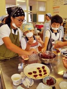 スモモのジャムをたっぷり乗せたお菓子を盛り付ける児童=11日、大棚小学校