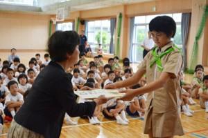 人権擁護委員からヒマワリの種を受け取る児童=8日、奄美市笠利町の赤木名小学校