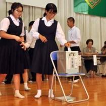模擬投票で意中の候補に一票を投じる生徒=2日、奄美市名瀬の県立大島高校