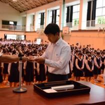 榊署長から指定書を受け取る生徒会の平勝範会長(中央)=27日、大島高校体育館