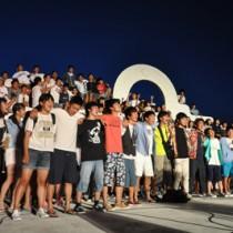 地元バンドのリードで夜空に歌声を響かせる成立学園の生徒たち=16日午後8時ごろ、与論町茶花