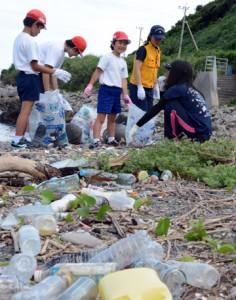 海岸のごみを集める円小児童と海保職員=11日、龍郷町円海岸