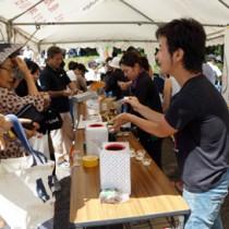 地域おこし協力隊によるソラマメしょうゆの試食ブースも人気を集めたしま興し祭り=25日、喜界町