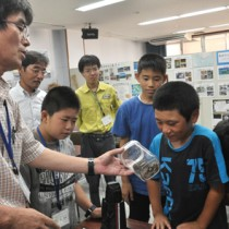 子ハブの入った容器を興味津々で観察する児童ら=19日、瀬戸内町立図書館・郷土館