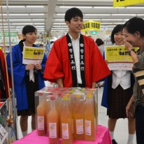 買い物客にオリジナルリキュールの説明をする奄美高校の生徒たち=24日、龍郷町