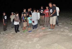 ウミガメの上陸跡を観察し、種類別の特徴などに理解を深めた参加者=10日夜、龍郷町安木屋場海岸