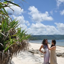 梅雨明けの青空の下、ビーチでくつろぐ観光客ら=18日、奄美市名瀬の大浜海岸