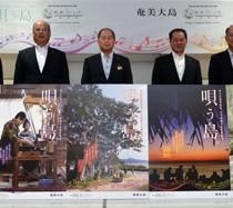 「あまみっけ。」のポスターを喜ぶ奄美大島5市町村長ら=1日、奄美市名瀬