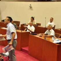 芦徳の客船寄港地整備計画について説明を受ける龍郷町議ら=24日、龍郷町役場議場