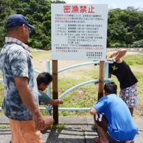 立て看板の設置作業をする笠利地区漁業集落メンバー=11日、奄美市笠利町