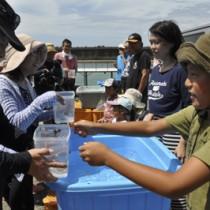 サンゴ株をダイバー(左側)に引き渡す出資者と、サンゴ株=16日、知名町沖泊漁港