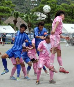 【サッカー予選】ゴール前で競り合う和泊と大和の選手=16日、龍郷町中央グラウンド