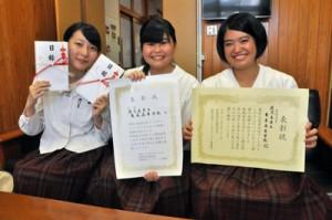 ダブル受賞を報告する(左から)山田愛さん、川村あみさん、福島珠緒さん=29日、奄美高校