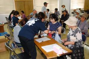 「ご長寿応援券」の申請を行う高齢者ら=5日、奄美市役所