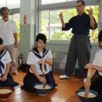 棚橋さん(右奥)の指導ですりゴマ作りを体験する生徒ら=9日、瀬戸内町の俵中学校