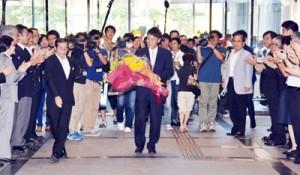 職員の拍手に迎えられて初登庁する三反園知事(中央)=28日、鹿児島市の県庁