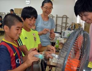 ペットボトルのミニ風力発電機作りなどで地球温暖化問題について理解を深めた児童ら=18日、奄美市役所