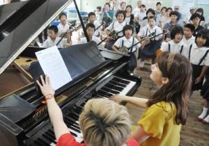 児童らの三味線、島唄と共演したピアノデュオ「デュエットゥ」のコンサート=13日、伊仙町の鹿浦小学校