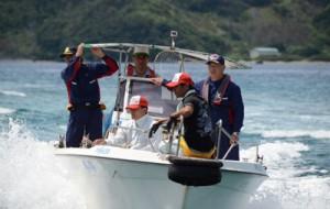船上から西原半島を視察する徳田町長(写真右)=27日、龍郷町