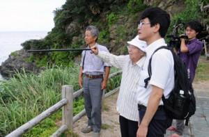 大島さん(左から2番目)の案内で遺体を埋めた場所を確認する調査団メンバー=25日、宇検村の船越海岸
