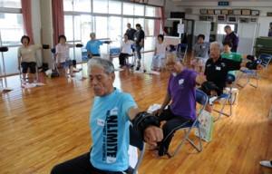 いきいきどぅくさ体操教室で、歌に合わせてゆっくりと腕を上げる参加者=6月23日、宇検村芦検