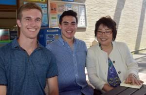 出水沢さんを取材したマイケルさん(中央)とジャスティンさん=21日、鹿児島市