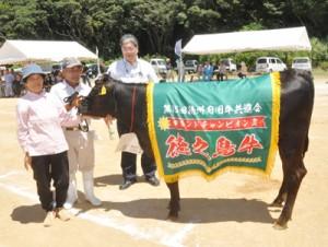 グランドチャンピオンに輝いた時山宏吉さん(左から2人目)の「こう号」=24日、天城町のJAあまみ徳之島中央家畜市場