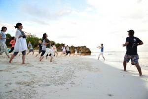 早朝、宿泊先のホテル近くの浜で呼吸体操するツアー参加者=6日、与論町(主催者提供)