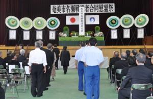 恒久平和への願いを込めて焼香する参列者=15日、奄美市の名瀬小学校体育館