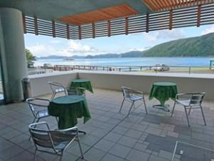 カフェがオープンした加計呂麻島展示・体験交流館(上)と、「地元の人とたくさん交流したい」と来店を呼び掛ける大学生たち=瀬戸内町諸鈍