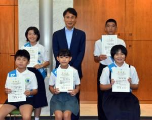 任命証を手に撮影するかごしまこども環境大臣(前列右が德重さん、後列左が鬼塚さん)=5日、鹿児島市の県庁
