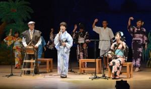 「渡しゃ」を歌った松山美枝子さん(前列中央)。子どもたちの八月踊りが祭り気分を演出した=4日、奄美文化センター