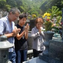 墓前で手を合わせ、先祖らの霊を自宅に伴う家族連れ=15日、奄美市名瀬の永田墓地