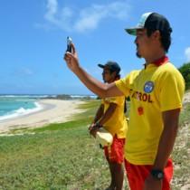 配信動画を撮影する奄美ライフセービングクラブの西さん(写真右)=24日、奄美市笠利町の土盛海岸